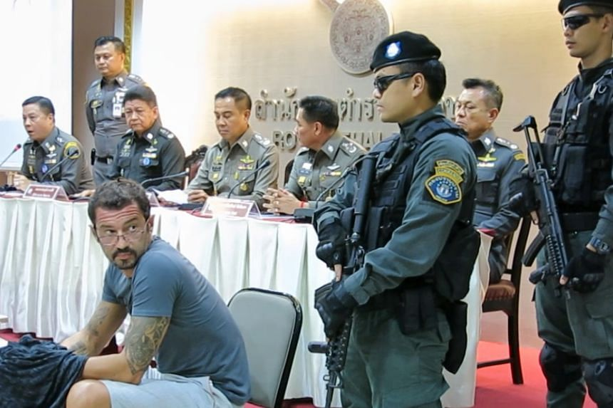 Swiss national Xavier Andre Justo (in T-shirt), a former PetroSaudi employee, being presented at a press conference at the Royal Thai Police head office, following his arrest for blackmail.