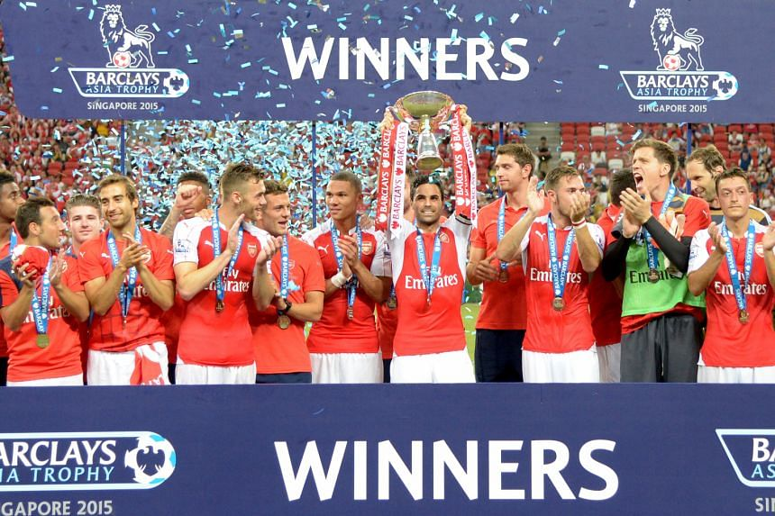 Arsenal club skipper Mikel Arteta lifting the Barclays Asia Trophy as his team-mates celebrate. Everton goalkeeper Joel Robles and right-back Seamus Coleman watching helplessly as Theo Walcott's shot crosses the line to give Arsenal a 1-0 lead.