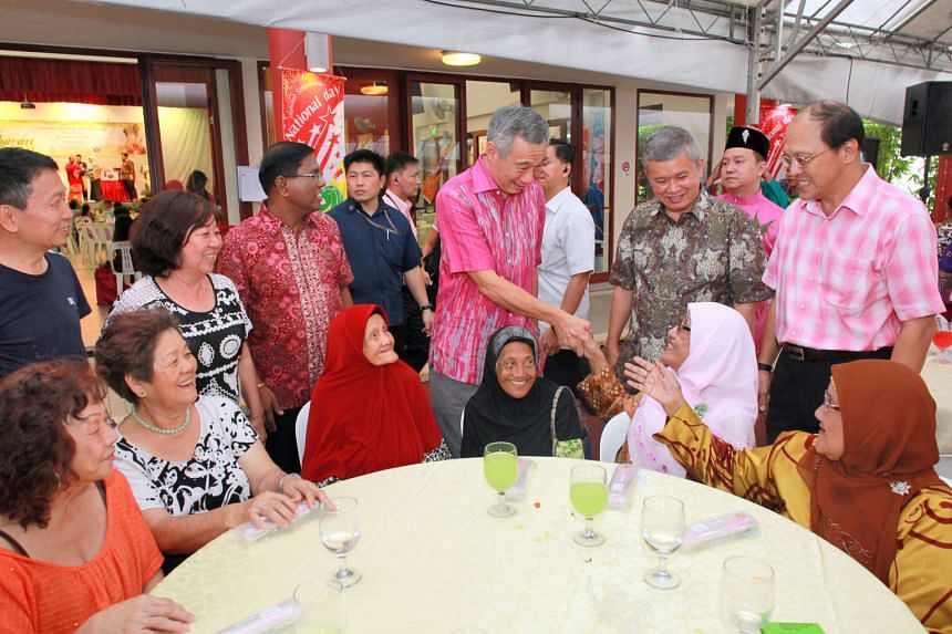 Prime Minister Lee Hsien Loong, with Ang Mo Kio GRC MP Ang Hin Kee (second from right) and grassroots leaders, meeting residents at Cheng San Community Club yesterday.