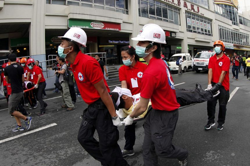 A Filipino rescuer (left) conducting a high-angle rescue operation during an earthquake preparedness drill yesterday at a building in Makati City, south of the Philippines' capital Manila. Thousands of people took part in the drill (above) to prepare