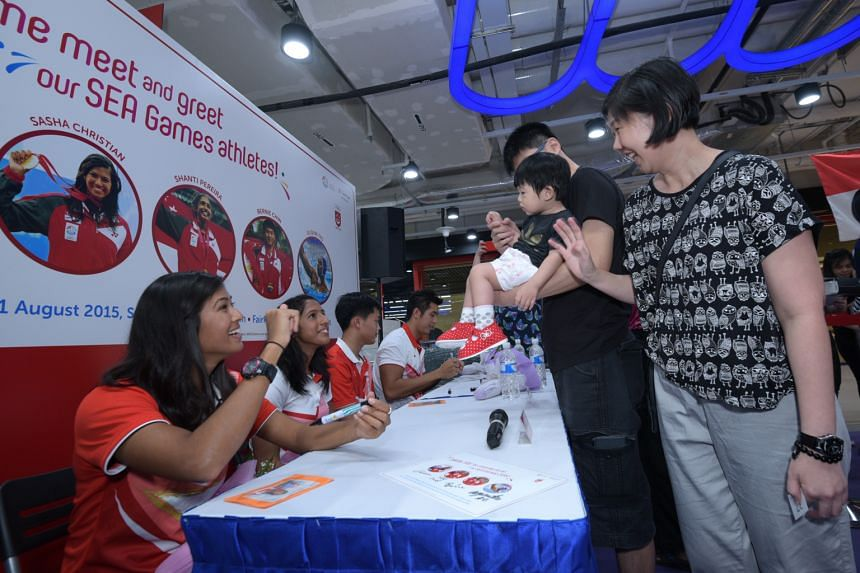 Team Singapore athletes (from left) Sasha Christian, Shanti Pereira, Bernie Chin and Eugene Teo signed autographs for supporters at the NTUC FairPrice supermarket at Kallang Wave mall yesterday. The event was to celebrate the athletes' superb perform
