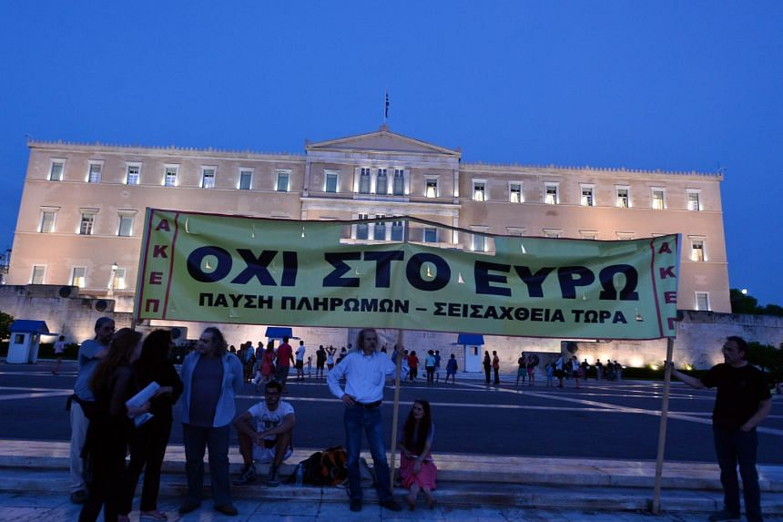 """Demonstrators displaying a banner saying """"No to Euro"""" in front of the Greek Parliament as lawmakers inside prepared to vote on a bailout package for the country. The deal will help Greece avoid a default next week when a payment to the European Centr"""