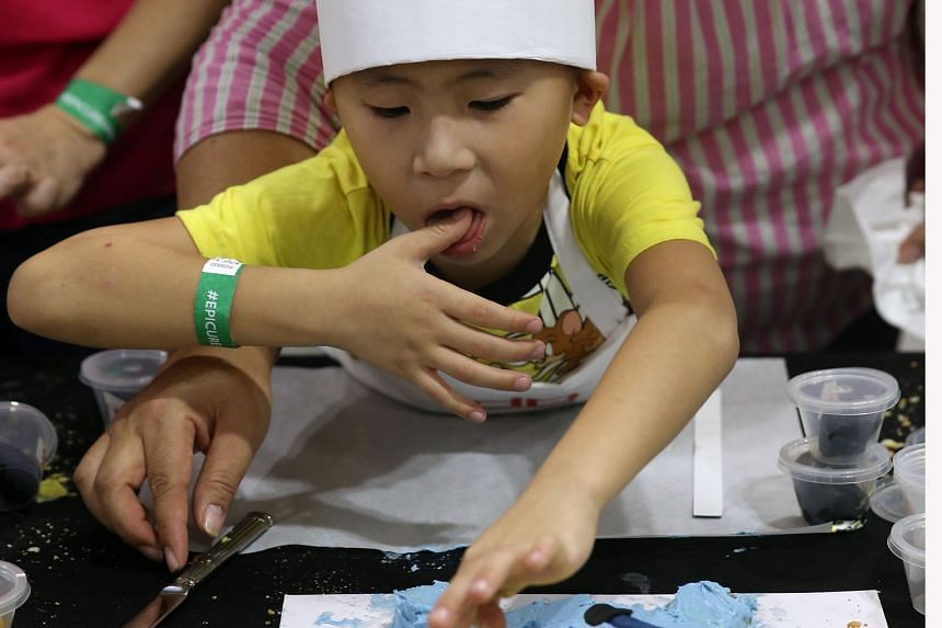 It's finger licking good as Brendon Au, seven, puts the finishing touches to his Minion cake. He was one of 33 children who took part yesterday in the junior pastry chef masterclass, conducted by executive pastry chef Benjamin Siwek of db bistro & Oy