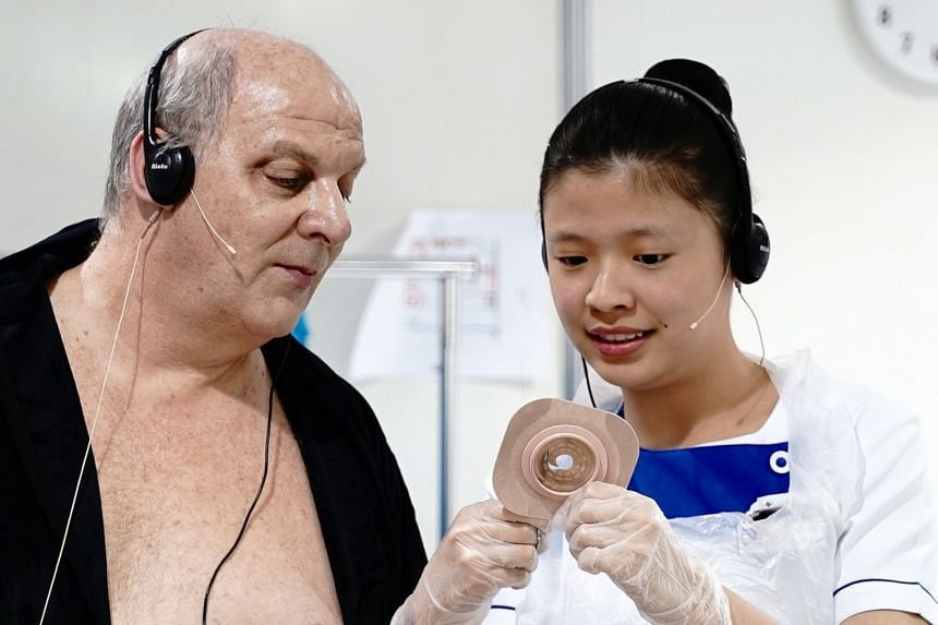 """Ms Lim Ling, a second-year student from Nanyang Polytechnic, seen here with her """"patient"""" at at the biennial WorldSkills contest, dubbed the """"Olympics of Skills"""". She took the bronze medal in the health and social care category."""
