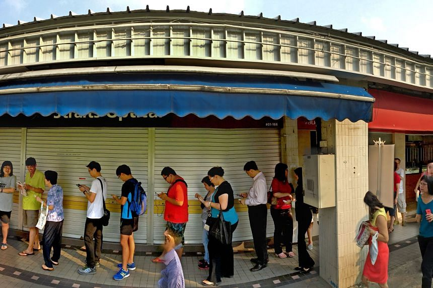 People waiting in line at POSB's Tampines Central branch yesterday to exchange currency notes for the new commemorative SG50 ones. The queue at some places like DBS Bank in Junction 8 was up to six hours long.