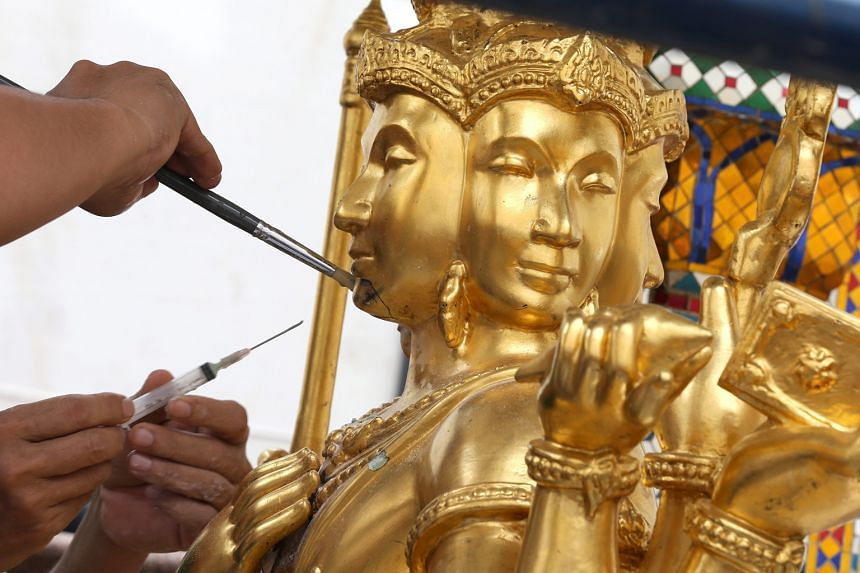 Craftsmen repairing the statue of the Hindu god of creation damaged during the bomb attack at the Erawan shrine in Bangkok on Aug 17.