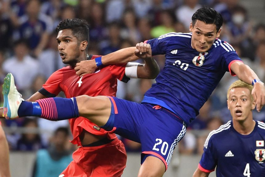 Hariss Harun (left) tussling with Japan's Tomoaki Makino during the 0-0 World Cup qualifier draw in Saitama in June. The Singapore vice-captain expects his side to keep up their good form against Syria.