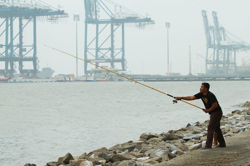 A man persevering with his fishing despite the poor visibility near North Port, in Port Klang, on Tuesday afternoon.