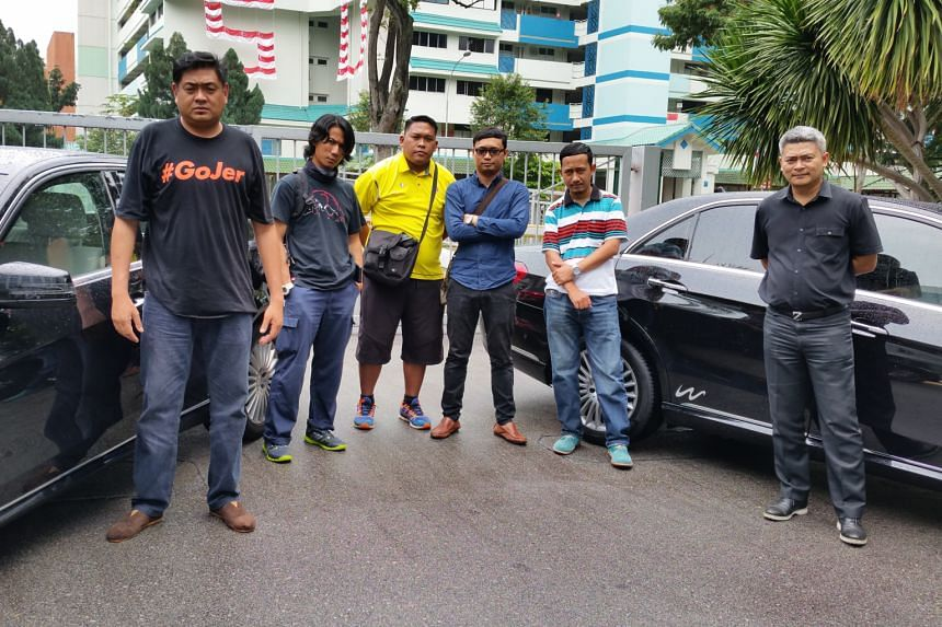 """Disgruntled drivers of limousine company Wolero posing beside two of the company's Mercedes cars. They say they are acting on advice from the Land Transport Authority that """"individual parties are not allowed to lease/rent private hire cars from car r"""
