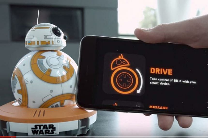 Fans dressed as Star Wars characters pick new toys from the upcoming film in Hong Kong (left) while BB-8 (above) is set to be the movie's most beloved robot following the toy's launch yesterday. With a smartphone as a controller, users can steer it a