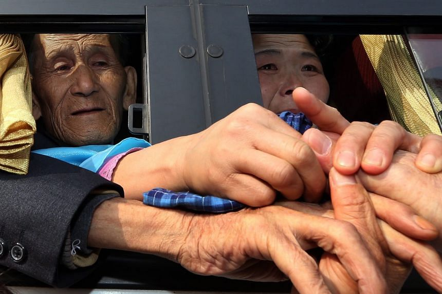 A file photo of separated families living in South Korea clasping the hands of their North Korean relatives inside a bus after a brief reunion. Such reunions are hugely emotional affairs for the largely elderly participants.