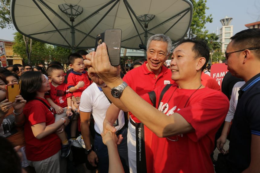 PM Lee Hsien Loong posing with a member of the public for a photograph at yesterday's Families for Life Celebrations. Mr Lee and his wife Ho Ching were among the 20,000 or so people at the event.