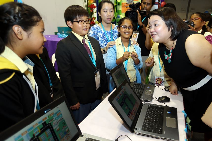 Ms Tan Swee Leng (right) of the People's Association, chatting with pupils yesterday at the Singapore Science Centre, where the children from Primary 4 to 6 showed the digital games they produced using a simple coding tool called Scratch to create ga