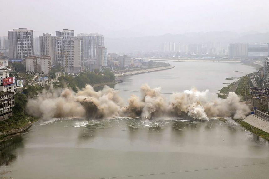 The bridge, built in 1971, was 246.6m long and 12m wide. A new one will be constructed at the same location as a replacement, the local media reported. (From top) A series of photos captures the Lishui bridge collapsing during a controlled demolition