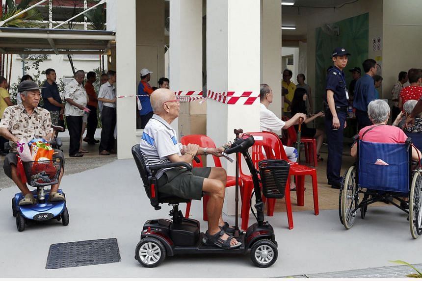 Above: Elderly voters, some in wheelchairs and motorised mobility devices, heading to vote at Block 62B in Toa Payoh Lorong 4.
