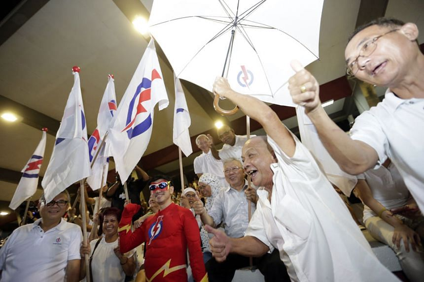 PAP supporters in high spirits at Toa Payoh Stadium, where they awaited the results of the polls last night.
