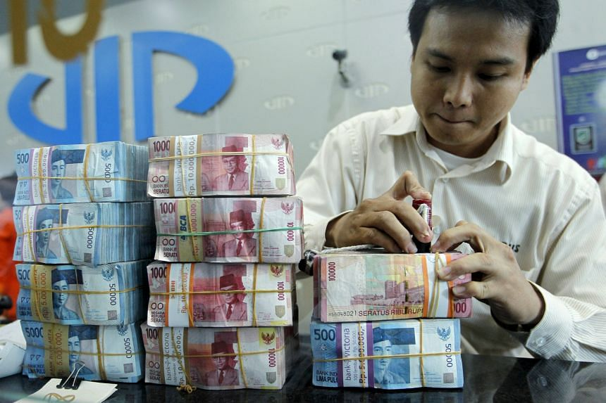Rupiah notes being prepared for customers at a money changer in Jakarta. The Indonesian currency, like the ringgit, has tumbled to the lowest levels seen in 17 years. Yesterday, it traded at 10,334.3 against the Singdollar.