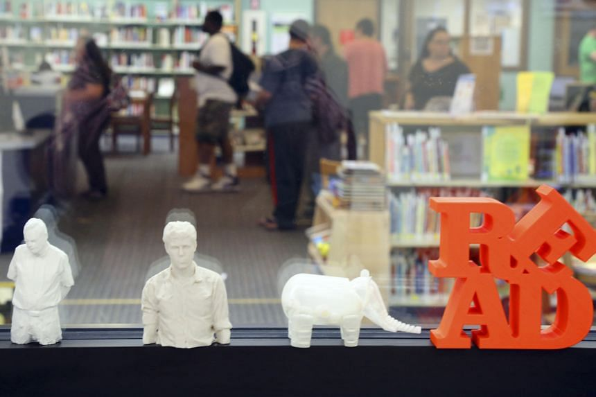 The library also carries guitars (far left) and a 3-D printer, which people have used to create different things (left). Sacramento Public Library's Rivkah K. Sass (above left) and Lori Easterwood with games, puppets and other items.
