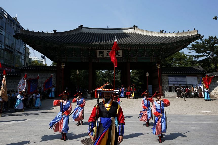 South Korean officials in Royal Guard uniforms performing the changing of the guard ceremony at Deoksugung Palace in Seoul, South Korea, yesterday. The ceremony is a popular spectacle for tourists in the capital city.