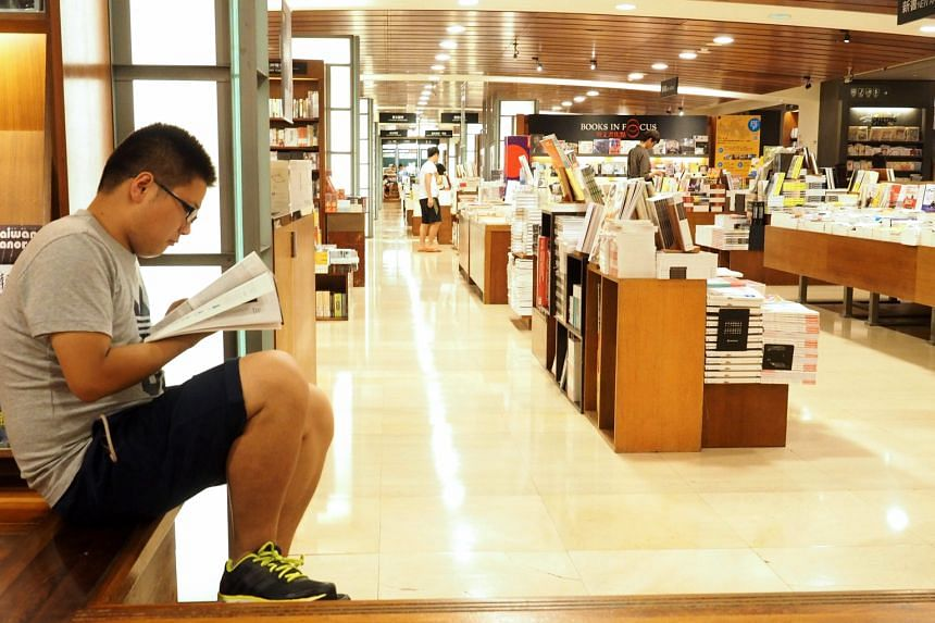 A young man reading at a book store in Taipei. According to surveys, young readers who are digital natives still prefer reading on paper.