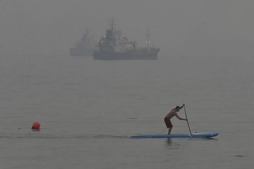 A man, undeterred by the air quality, on a paddle board at East Coast Park as the haze partly obscured ships in the distance at East Coast Park yesterday at around 6pm. NEA forecast the 24-hour PSI to be in the high end of the unhealthy range and low
