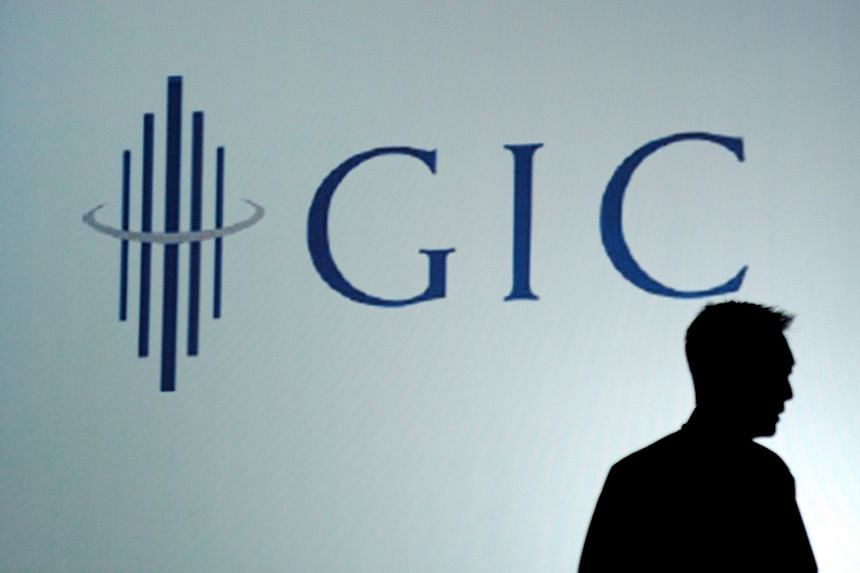An employee silhouetted against the GIC logo. The fund was part of a consortium of investors that accounted for the biggest deal of the third quarter.