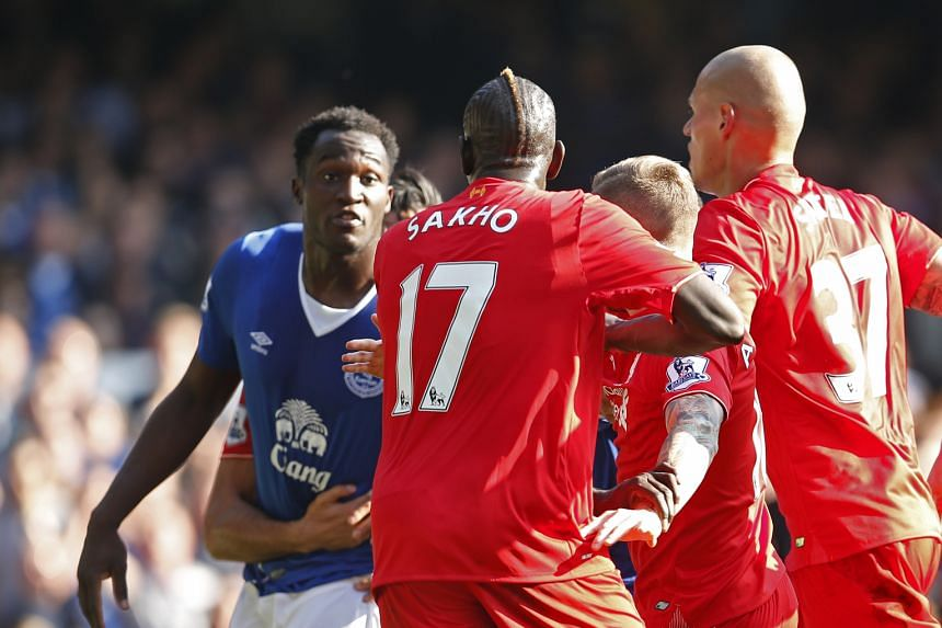 Above: Romelu Lukaku scoring the equaliser for Everton. The Belgian striker was nevertheless disappointed as he thought it was a great chance to beat Liverpool. Left: As with a Merseyside derby, thing got a bit testy during the match with this flare-