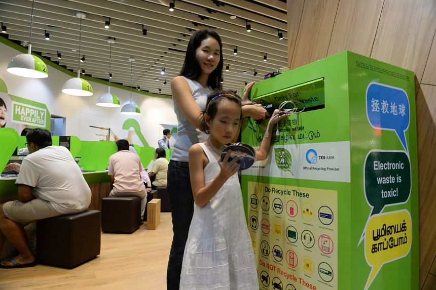 Ms Bernadette Ng and her daughter, Clare Tan Min, eight, dropping several old electronic items in the recycling box at the StarHub outlet in Tampines Mall. Ms Ng says she makes it a point to have her children present when she donates recyclables.