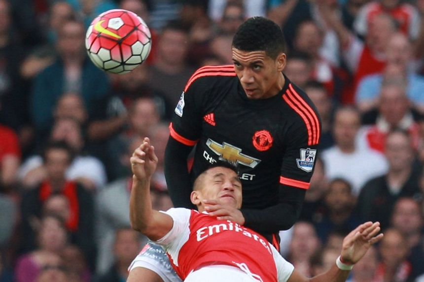 Above: Captain Wayne Rooney cuts a frustrated figure after United are outplayed and outwitted. Left: United defender Chris Smalling had to resort to roughhouse tactics in a bid to stop Arsenal forward Alexis Sanchez. But the Chilean has the last laug