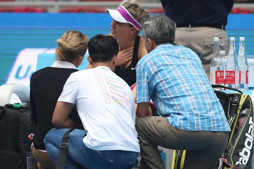 Eugenie Bouchard being attended to after she felt dizzy during her first-round match against Andrea Petkovic at the China Open yesterday. The Canadian, playing in her first tournament since slamming her head in a locker-room fall at the US Open, late