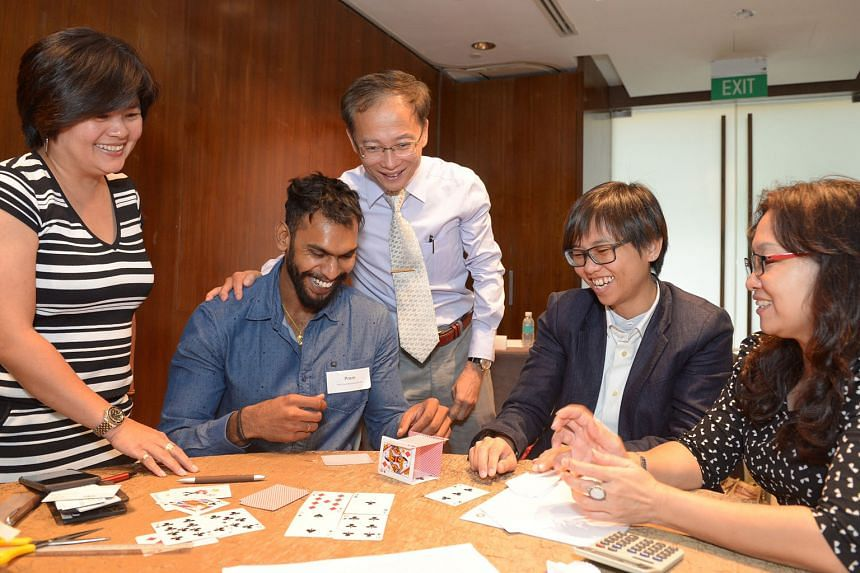 Nanyang Business School lecturer Clive Choo (centre) with participants (from left) Mrs Josephine Low, Mr Prem Roy, Ms Ang Ee Li and Ms Sharon Goh in a prototype-building exercise.