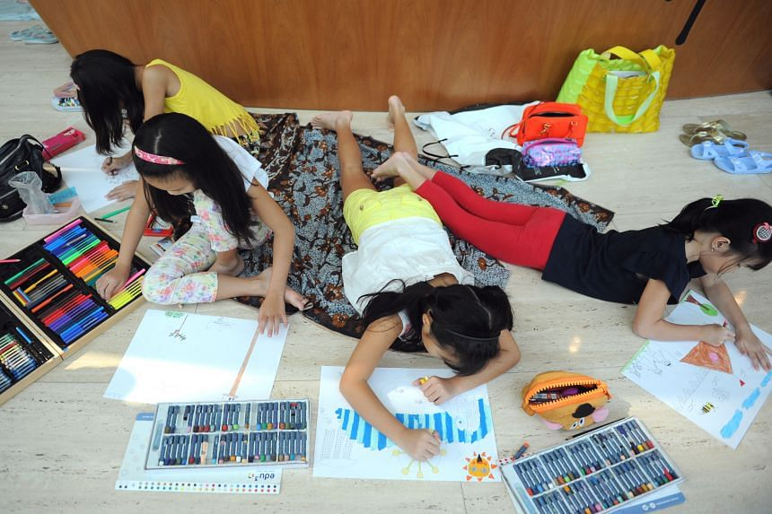 Tasha Liew (from left), nine; Tyra Liew, seven; Keira Wong, eight; and Khloe Wong, five, engrossed in their work during a Children's Day drawing competition at the Esplanade yesterday. About 1,500 children aged two to 12 took part in the competition