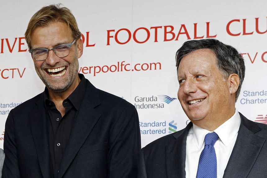 New Liverpool manager Juergen Klopp (left) sharing a laugh with club chairman Tom Werner at a press conference last Friday. The German says that while he is not under pressure to deliver in his first season, he has been tasked with getting the Reds t