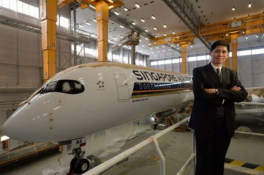 Mr Tan Pee Teck, with SIA's new A-350, which is being painted in the carrier's colours at the Airbus paint shop in Toulouse, France, yesterday. The airline has 63 A-350s on order. After the first jet arrives in January, another 10 are scheduled to be