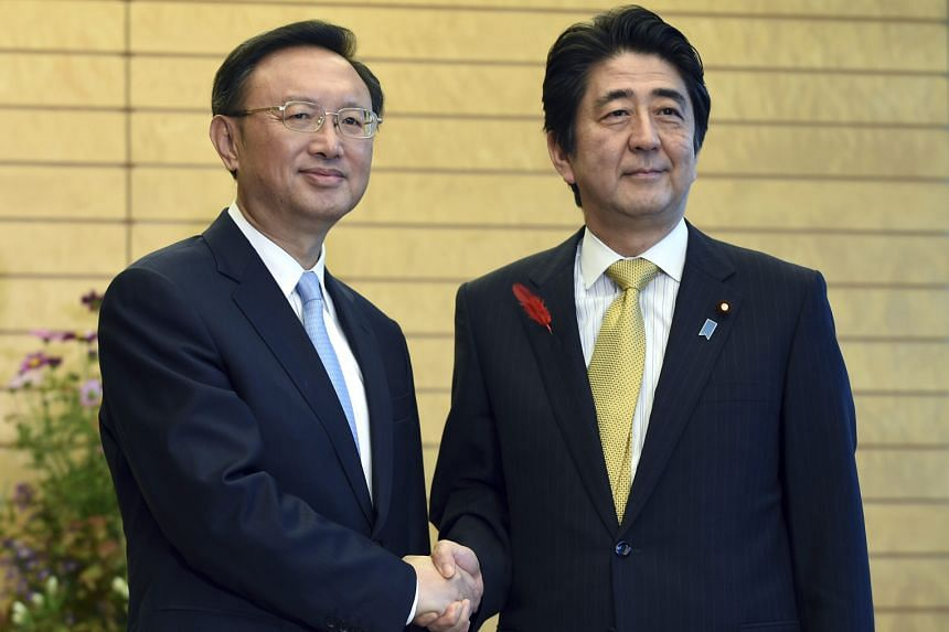 """Chinese diplomat Yang Jiechi and Japanese Premier Shinzo Abe (right) had a """"warm and friendly"""" meeting yesterday."""