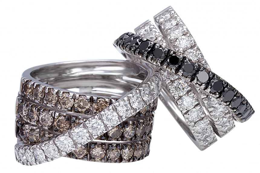 Italy: Ring with white and brown diamonds in 18K white gold (left, $6,470), ring with white and black diamonds in 18K white gold (right, $3,360) both by Orital.