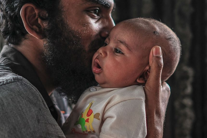 A Rohingya man holding his daughter while waiting near the United Nations High Commissioner for Refugees (UNHCR) office in Kuala Lumpur in August. A rumour about refugee status cards being issued by the UNHCR saw hundreds of Rohingya refugees throng