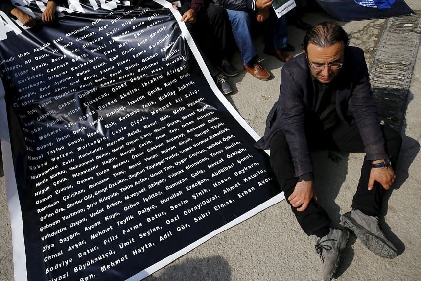 A man sitting beside a list of names of those killed in last Saturday's suicide bombings, during a commemoration event in Ankara. The latest attack has heaped pressure on the government, which is already under fire for failing to provide more informa