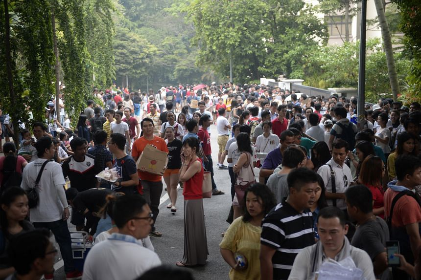 The queue outside the Myanmar Embassy yesterday, with some people giving out free food and drinks to those waiting in line. Unlike the scenes of confusion on Saturday, yesterday's crowd arrived prepared for the long wait.