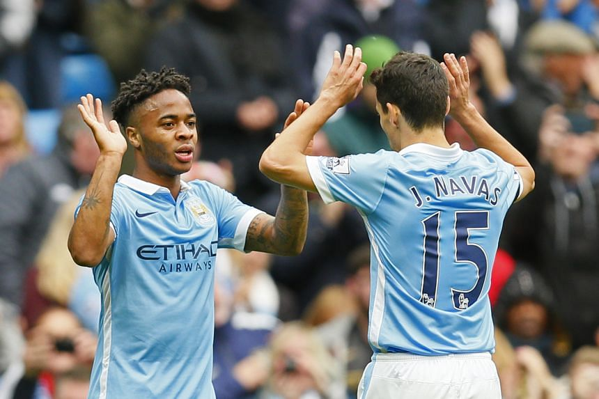Manchester City's Raheem Sterling celebrating his hat-trick with Jesus Navas. The 5-1 win kept the team on top of the league.