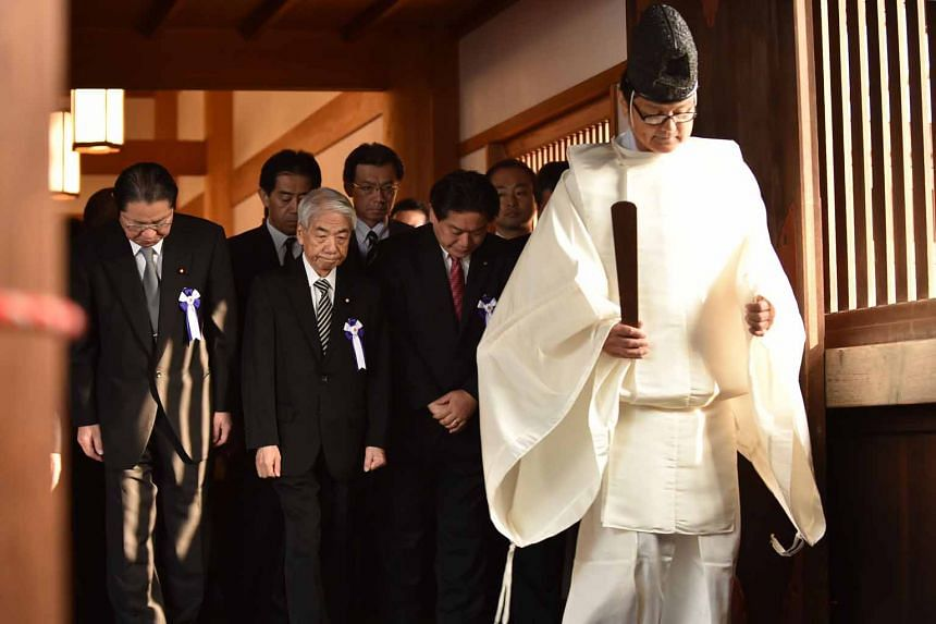 Japanese lawmakers following a Shinto priest during a visit to the controversial Yasukuni shrine yesterday.