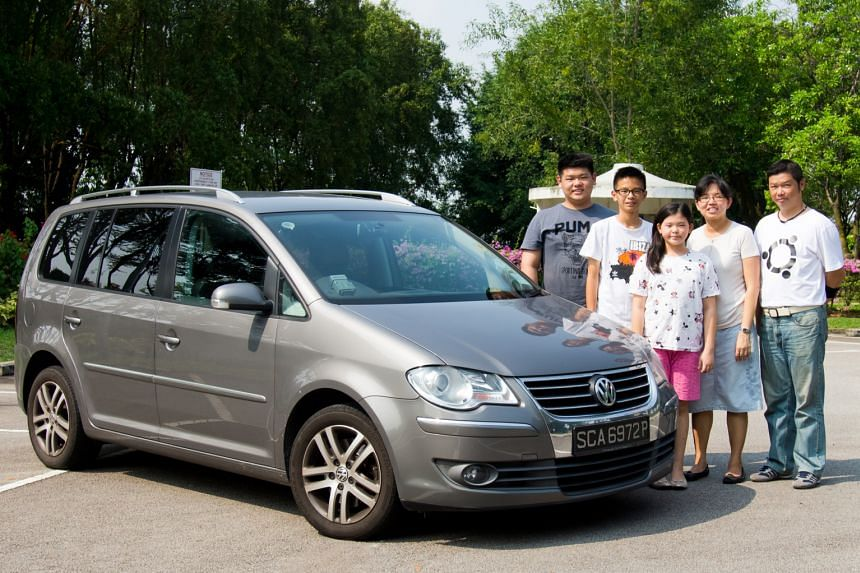Mr Nicholas Ng (right), wife Liping and their children (from far left) Nicodemus, Nathan and Lydia with their family car.