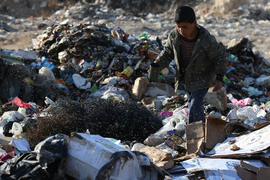 A Syrian boy scavenging through rubbish in the rebel-held part of Aleppo on Tuesday. Prices of basic goods are soaring after an extremist advance cut off the sole route to the city's regime-held areas.