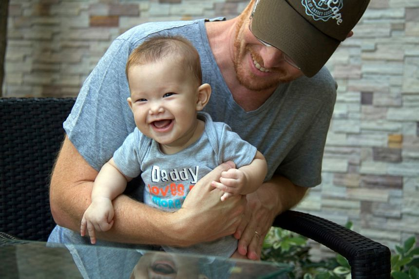 Mr Gordon Lake with baby Carmen who was delivered via Thai surrogate Patidta Kusolsang. Mr Lake and his husband are fighting for parental rights over Carmen, which Ms Patidta refuses to cede.