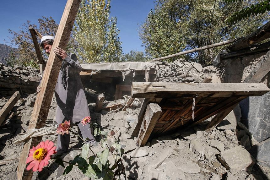 A man removing debris from what is left of his home at Hinjol village in Chitral valley, Pakistan, yesterday. Thousands of survivors sharing his plight are desperate to rebuild their homes quickly before winter sets in. The quake damaged about 14,000