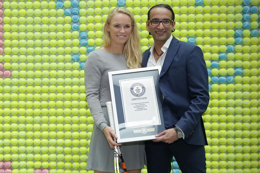 Former tennis world No. 1 Caroline Wozniacki, the brand ambassador for pharmaceutical firm Mundipharma, poses in front of the world's largest tennis ball mosaic with the firm's president (emerging markets), Raman Singh.