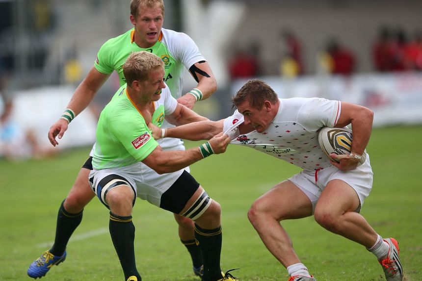 South Africa Sevens Academy team captain Kyle Brown (left) tackling an England Academy player en route to beating them 24-0 on day two of the Societe Generale Singapore Cricket Club International Rugby Sevens at the Padang. The tournament favourites