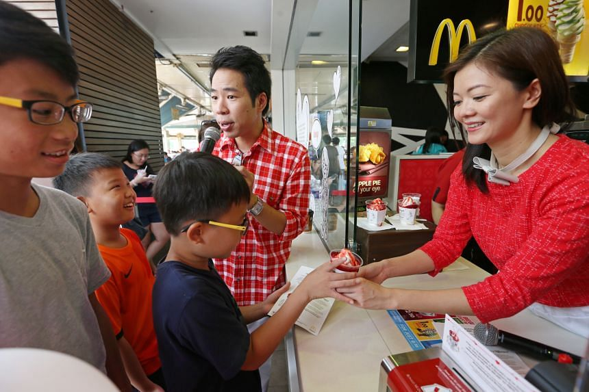 Local celebrities Chua En Lai and Michelle Chong selling strawberry sundaes to (from left) Ethan Loh-Chan, 12, Ernest Tan, nine, and Ethan Tan, 12, at a McDonald's in Ang Mo Kio yesterday. From Nov 1 to 15, McDonald's will donate $1 from every strawb