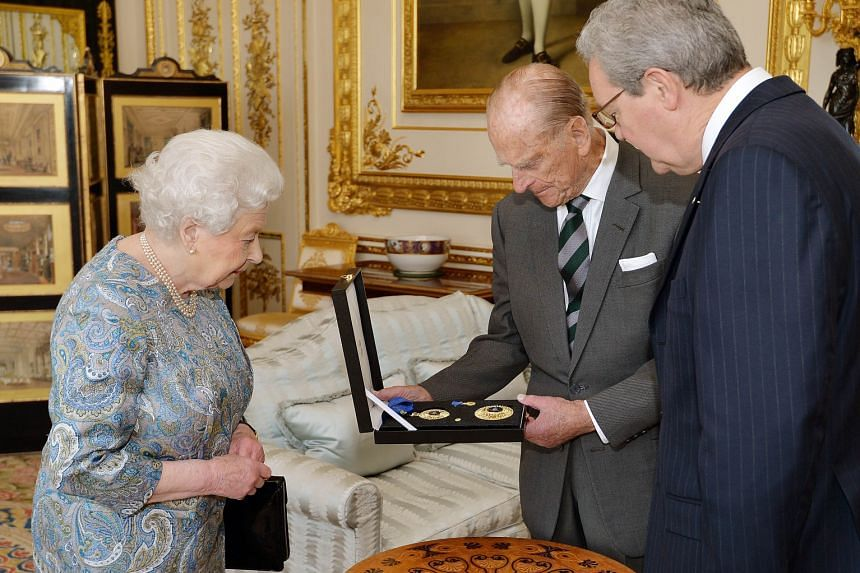 Britain's Prince Philip (centre) being presented an insignia of a Knight of the Order of Australia on April 22 by Queen Elizabeth (left) as Australian High Commissioner Alexander Downer looked on.