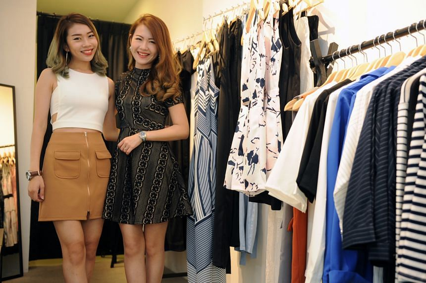 Sisters Jolene (left), 25, and Lucinda Zhou, 27, at their pop-up store in Boufe, a cafe in Tanglin Road, on Monday. They founded online store Ohvola in 2007 after working together selling dresses from a pushcart. As they were still studying then, the